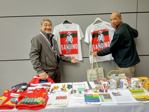 Jose Antonio and Johnny at NSCAG stall during NEU Conference with t-shirts of Augusto Cesar Sandino, national hero of Nicaragua